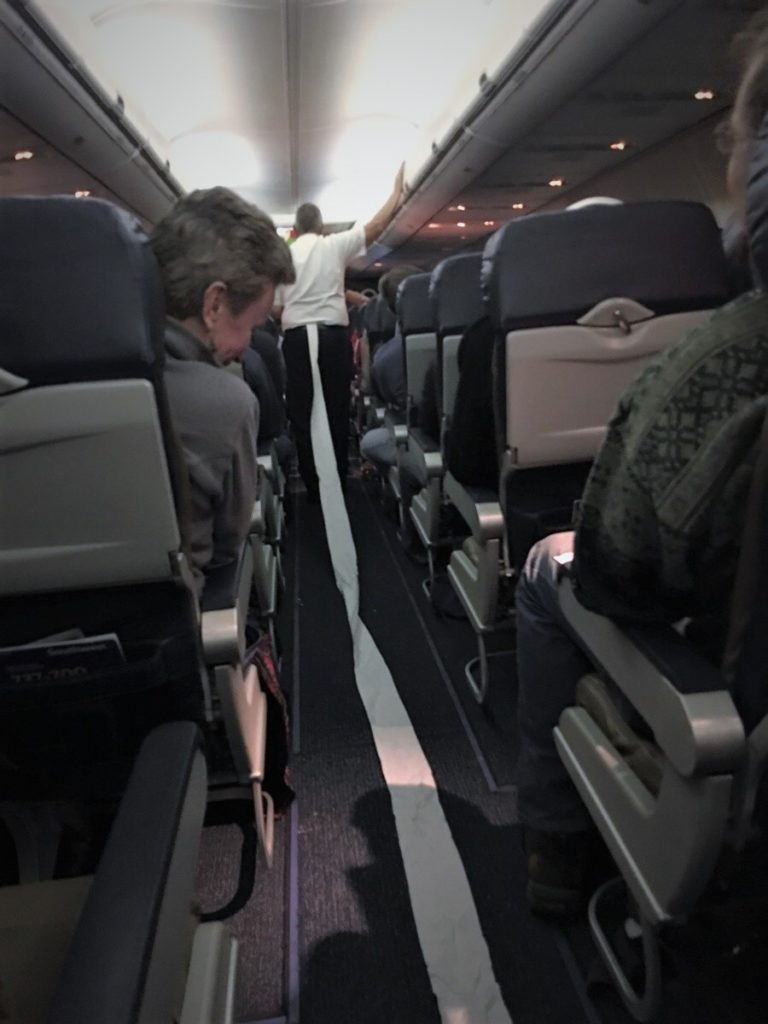 Man walking down the aisle of an airplane with toilet paper stuck in his pants.