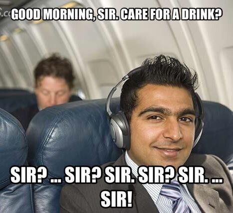 man in headphones ignoring flight attendant on a plane.