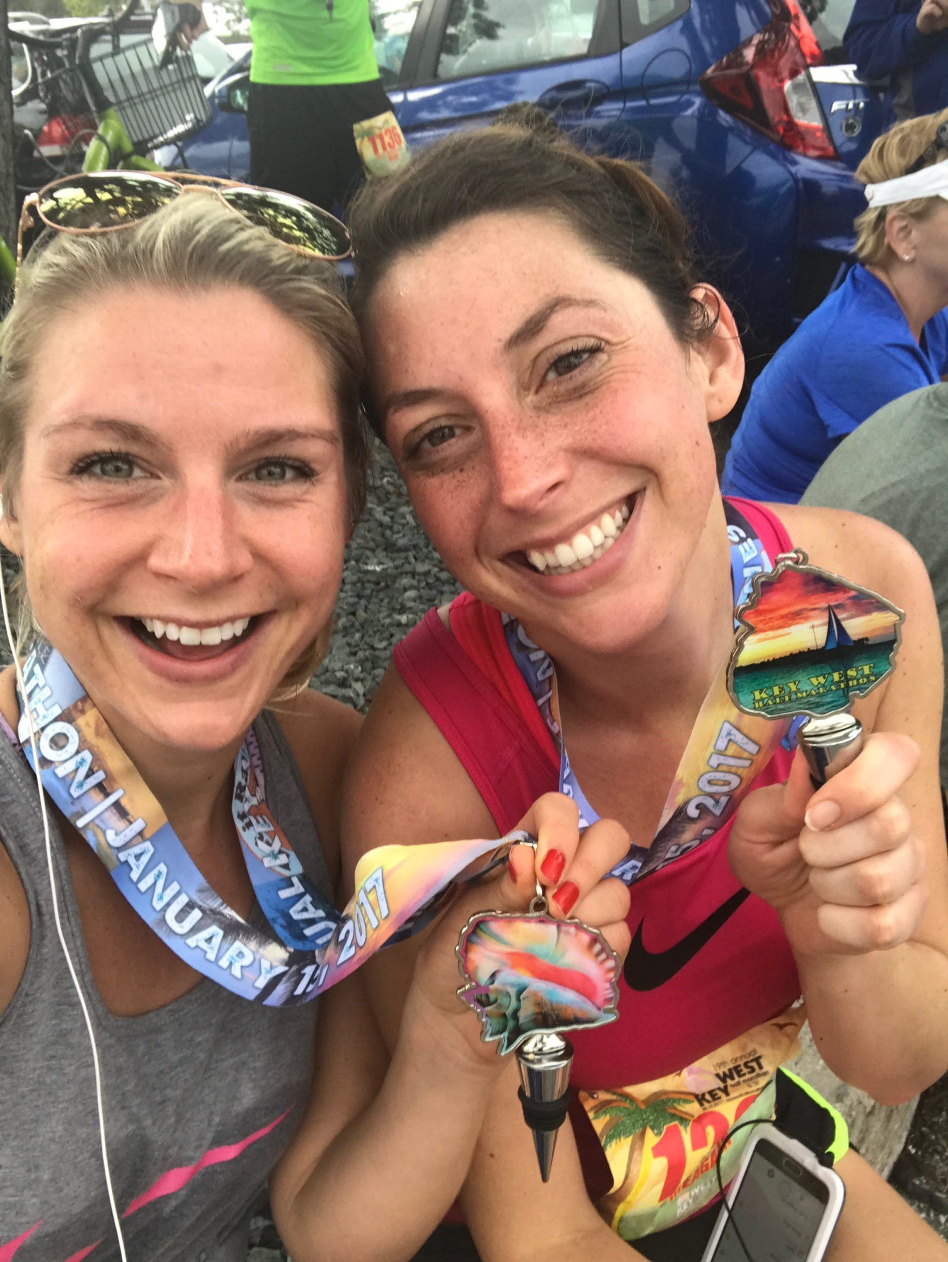 holding medals at Key West half marathon